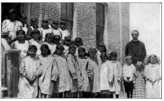 John Roberts was a priest and mission worker among the Shoshone and Arapahoe Indians in Wyoming, USA. He worked tirelessly from his arrival in 1883 to his death in 1949. Above, in 1906, with students at his Fort Washakie Mission School for girls, which complemented a nearby government school for boys.