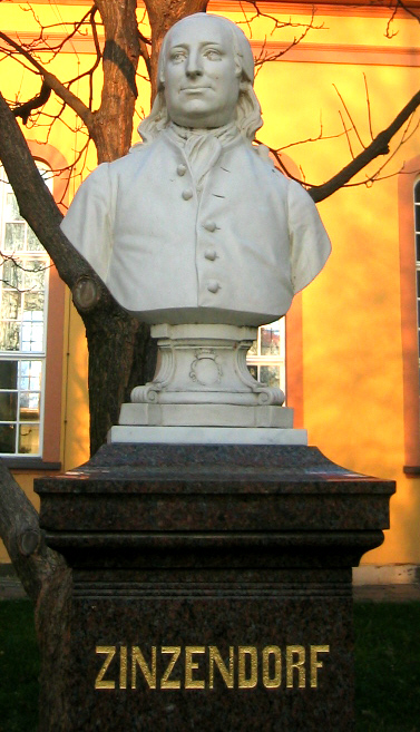 """Count Nicolaus von Zinzendorf developed a personal """"theology of the heart,"""" which led him to shelter Czech Protestants of the Unitas Fratrum (Bohemian Brethren, or Moravians). They developed a rich liturgical and devotional life, for which he wrote many hymns, and a zeal for missionary activity. In the Pennsylvania colony (USA) he tried to bring together many denominations in unity. This monument stands in Herrnhut, Germany, the Moravian village on his estate."""
