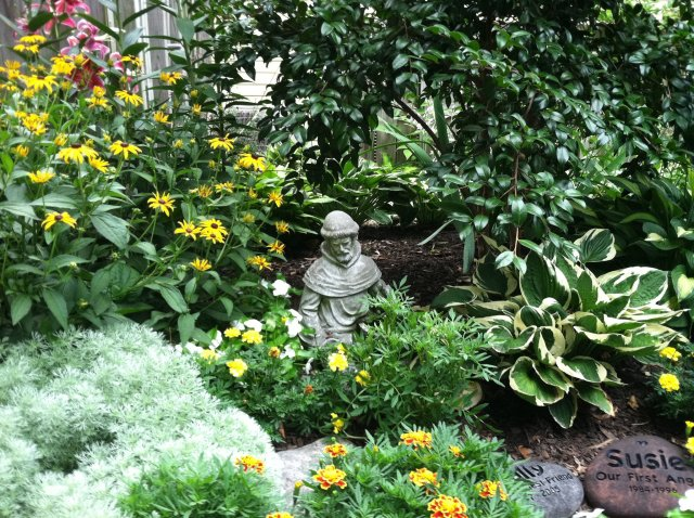 St. Francis statue watches over a flower garden in Maryland where two beloved pets are buried. (William Thomas)