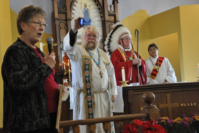 Julia Chester Emery's best-known legacy is the United Thank Offering, a fundraising ministry of the Episcopal Churchwomen, which has raised hundreds of millions of dollars to build and rebuild churches and support mission work all over the world. Above, from 2013: Michael Smith, the Bishop of South Dakota, wearing the feathers of a Sioux chief instead of his mitre, presided over the consecration of the new St. James's, Cannon Ball, North Dakota, as the Rector, John Floberg, holds up a famous UTO blue box. The program was instituted by Julia Chester Emery, who for 40 years presided over the Woman's Auxiliary (now Episcopal Church Women) of the Domestic and Foreign Missionary Society, which is the formal name of The Episcopal Church. St. James's lost its former building to a teenage arsonist three years earlier, but those blue boxes full of thanksgiving coins helped rebuild it better than ever. (Mary Frances Schjonberg/Episcopal News Service)