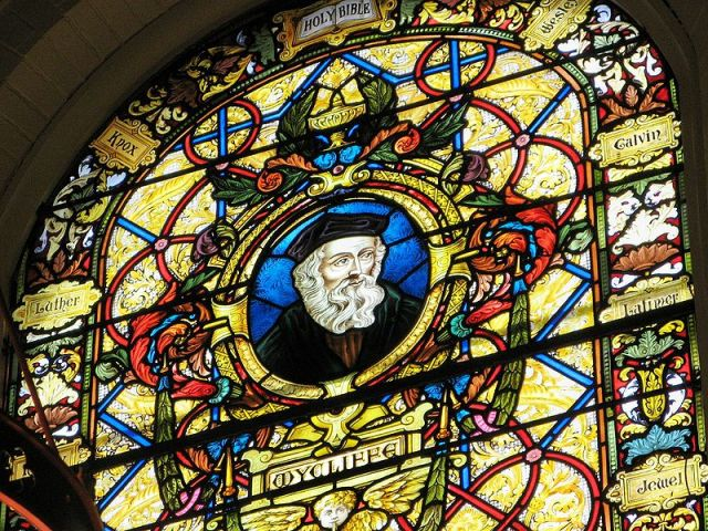 Wycklif window at Wycliffe College Chapel in Toronto; his name is spelled various ways. He was a professor of theology and philosophy at Oxford who questioned various Church doctrines; he believed strongly that laypeople should be able to read the Bible in their native language and translated the Vulgate into English. He supported the idea of a national church without international (papal) interference, and he taught that individuals could have a direct, unmediated relationship with God. But when he publicly doubted Transsubstantiation or the Real Presence of Christ in the Eucharist, he went too far for the times and was hounded out of office. (Wikipedia)
