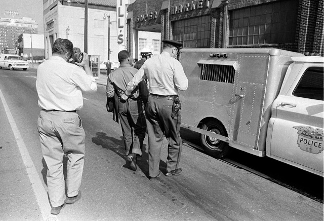 Dr. King, separated from Dr. Abernathy, led off to jail by the Birmingham Police in 1963. As you can see, King was not a tall man; the officers who confronted him towered high above. (Associated Press)