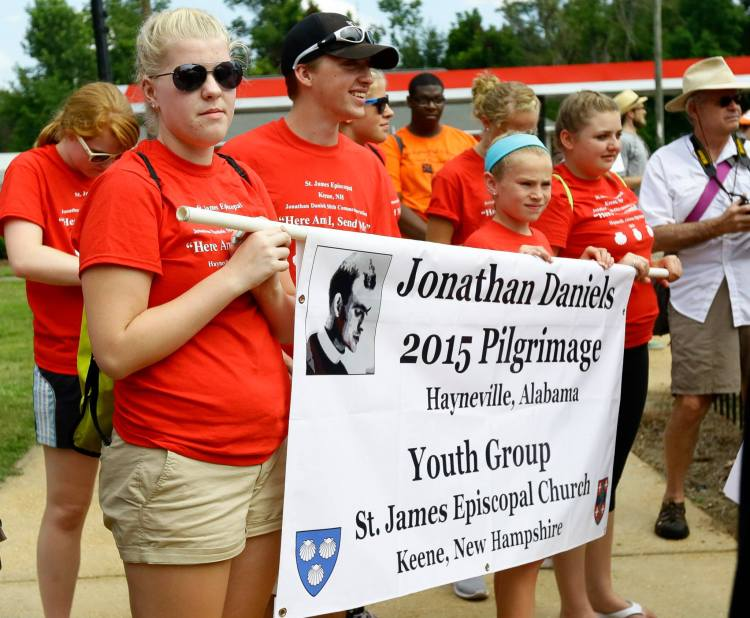 """The youth group at Jonathan Daniels' home parish marched Saturday at the pilgrimage in the civil rights martyr's honor in Hayneville, Alabama, wearing T-shirts reading, """"Here am I; send me."""" (parish photo)"""
