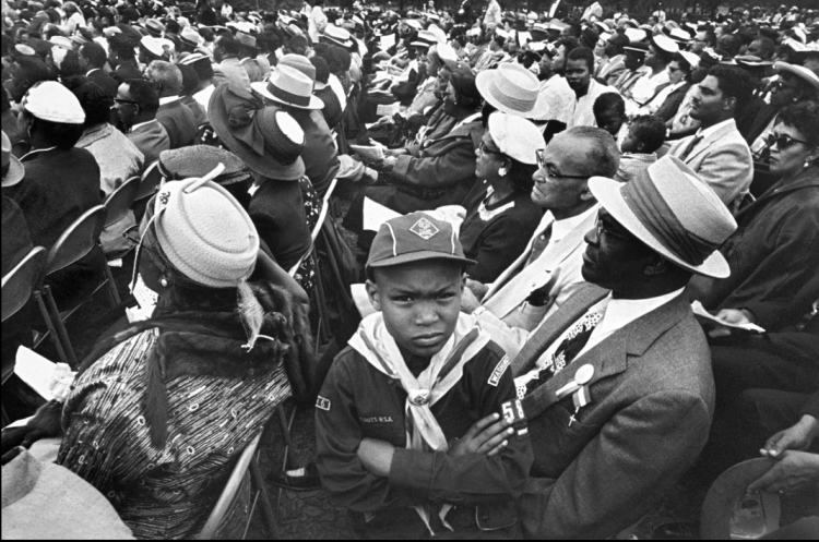 """The New York Times is publishing forgotten photographs for #BlackHistoryMonth, including this one showing a Cub Scout with his father at the 1957 Prayer Pilgrimage for Freedom march in Washington, D.C., on the third anniversary of the Supreme Court decision desegregating schools. The United States did not, of course, desegregate its schools, with many cities and states both North and South openly defying the court's order. The march was modest in size, with 25,000 attending, but young Dr. Martin Luther King Jr. delivered an important speech (""""Give Us the Ballot"""") and the pilgrimage presaged what was to come. Photographer Lee Friedlander, who later won a Guggenheim Fellowship and became very famous for his """"social landscape"""" shot, didn't focus on the VIPs up front, but on interesting people in the crowd - seated, peaceful, well-dressed, respectful. It makes you wonder what became of this little boy."""