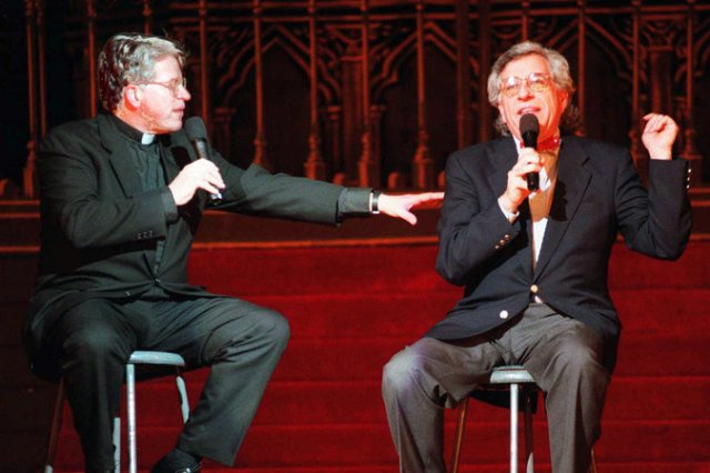 """Monsignor Thomas Hartman has died, a priest in New York who formed a media """"God Squad"""" with Rabbi Marc Gellman, which ran for two decades on television, radio and in newspapers and reached an audience of up to 15 million. With witty banter, they explored issues of faith and ethics across religious lines. They mostly avoided talking about Jesus, which would have divided them, but Gellman noted how much their separate traditions made them alike. """"We realized that we share identical ethical systems,"""" he continued. """"What God wants us to do in the world is the same: compassionate, forgiving, charitable, just. How we imagine God is different, but how we imagine what God wants us to do is exactly the same."""" Above: an appearance at Radio City Music Hall in 1997. (Bebeto Matthews/Associated Press)"""