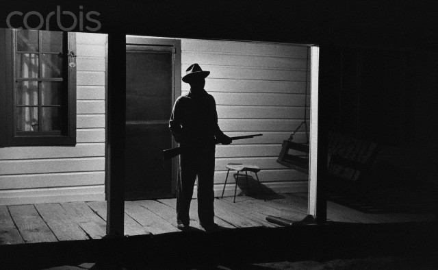 The Rev. Joseph Carter guarding his house at the end of a long dirt road from Klan members scattered in the woods around him, after he became the first African-American to register to vote in West Feliciana Parish, Louisiana in 1964. (Bob Adelman/Corbis