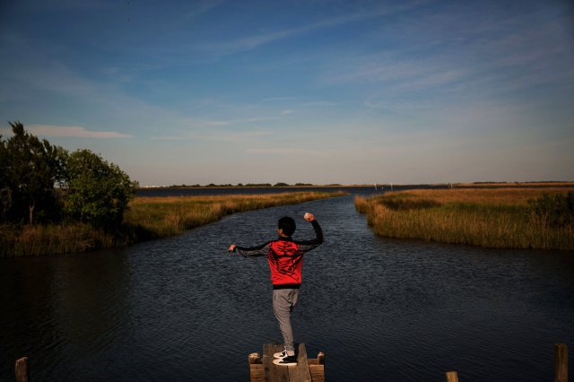 A boy throwing rocks into the bayou in Isle de Jean Charles. (Josh Haner/The New York Times)