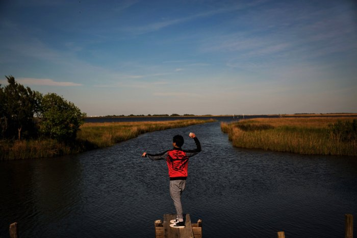 A boy throwing rocks into the bayou in Isle de Jean Charles. (Josh Haner/The New York Times)