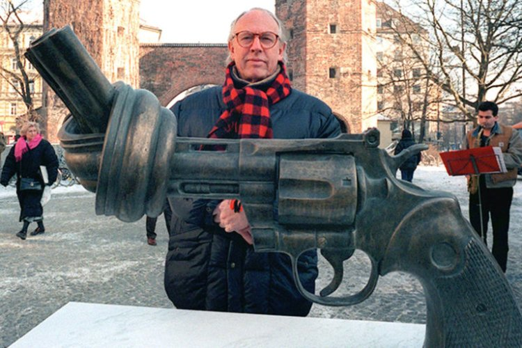 """Carl Fredrik Reutersward, the Swedish sculptor of """"Non-violence,"""" has died. Seen here in Munich with one of the copies of his iconic piece, he came up with the idea after John Lennon was shot. The original work was placed in New York's Central Park opposite the apartment building where Lennon was killed; now it's located at the United Nations headquarters, as well as 30 other cities around the world. We thought this was the best image we could show for Mother's Day. (Istvan Bajzat/Picture-Alliance/dpa)"""