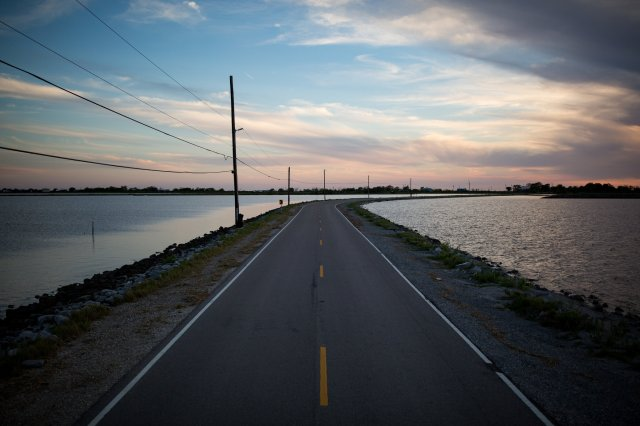 The United States is preparing to relocate 150 or so American Indians, the last residents of Isle de Jean Charles, Louisiana, as climate refugees; the island has lost 98% of its land mass since 1955 due to erosion, subsidence and sea level rise. Louisiana loses an area the size of Manhattan Island, New York, every year and the village can't be saved. The tribe has been working for 20 years or more on a relocation plan to move to dry land together as a community, but a few diehards don't want to go, which stymies the whole effort. The people know the land is being lost, but they just can't bring themselves to go. Once this causeway is gone, they'll be cut off. (Josh Haner/The New York Times)