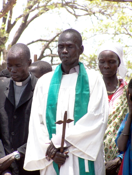 An Episcopal priest in South Sudan giving a public prayer. Today was chosen to commemorate the martyrs because on 16 May 1983, Anglican and Roman Catholic clergy signed a declaration that they would not abandon Christ even under threat of Shariah law. Persecutions increased in the next several years, including the murder of clergy and lay leaders, the burning of churches, hospitals, schools and Christian villages; and bombings at Sunday services. Mostly-Muslim Sudan and mostly-Christian South Sudan separated as a result of a plebiscite and subsequent treaty in 2011; civil war has continued in the South as tribes and political factions fight for control of oil and other resources. (David Copley)