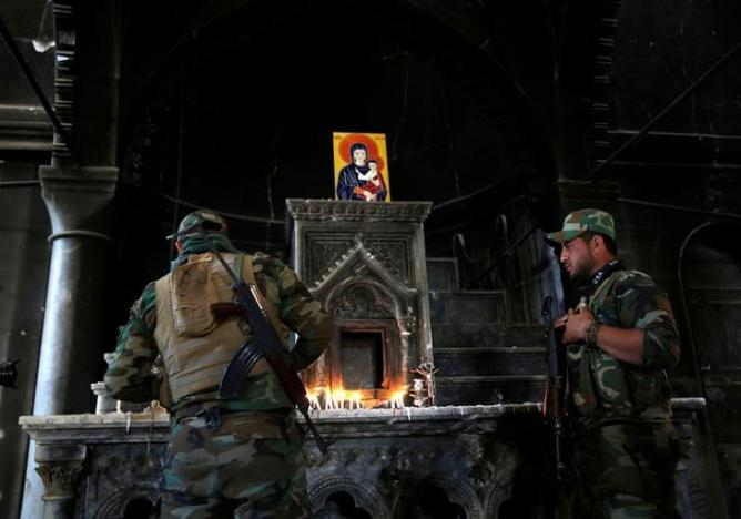 An Iraqi Christian soldier lights a candle during the first Sunday mass at the Grand Immaculate Church since it was recaptured from Islamic State in Qaraqosh, near Mosul in Iraq October 30, 2016. (Ahmed Jadallah/Reuters)