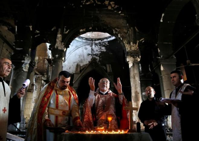 You've heard of the battle for Mosul, now raging; here was the scene a week ago, 30 October, when Christians were able to get back into their Church of the Immaculate Conception in nearby Qaraqosh, which was liberated first. The magnificent church has suffered heavy damage, but the clergy and people were able to celebrate Mass among the ruins. (Ahmed Jadallah/Reuters)