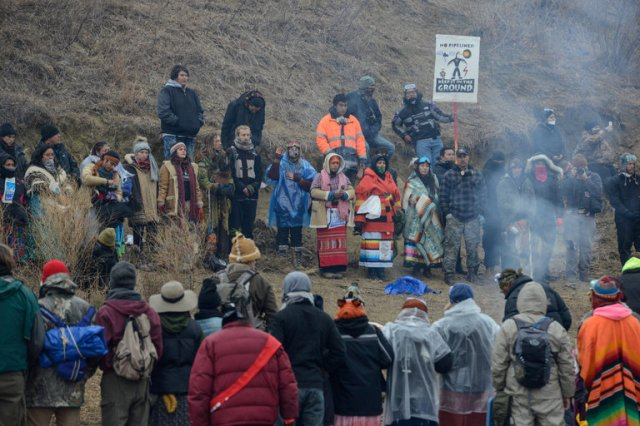 "The U.S. Army Corps of Engineers announced plans on Friday to close the Standing Rock oil pipeline protest camp, citing increasing violence between police and protesters. They want to move the Lakota Sioux demonstrators and their Native allies in 300 other tribes to a more convenient ""free speech zone"" that allows traffic to move. But this isn't likely to work; the Indians took the bridge for a reason, to disrupt the pipeline construction right next to their reservation and underneath their water supply. Standing Rock Chairman Dennis Archambault says the way to defuse the confrontation is to move the pipeline. Last week hundreds of demonstrators were injured, including one critically, in what looked like a police riot; the county sheriff has sided with the pipeline company and the white neighbors. (Stephanie Keith/Reuters)"
