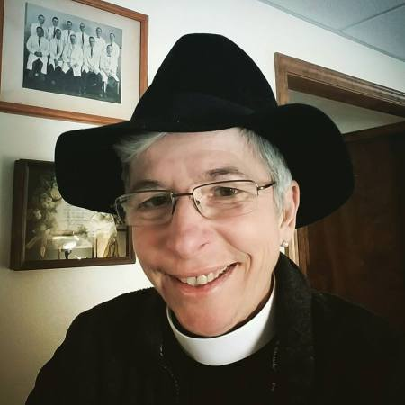 """Somebody gave our Missioner and newly-ordained deacon Maria L. Evans a hat on Sunday, and (no surprise) she's taken to it. We call this shot """"Missouri Jones and the Deacon of Doom"""" - and she took to that too."""