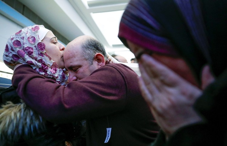 Syrian refugee Baraa Haj Khalaf (L) kisses her father Khaled as her mother Fattoum (R) cries after arriving at O'Hare International Airport in Chicago, Illinois, U.S. February 7, 2017. REUTERS/Kamil Krzaczynski     TPX IMAGES OF THE DAY - RTX302QE