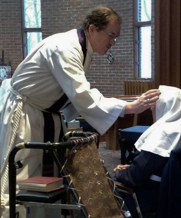 The Rev. Tom Fehr, Chaplain of the Community of the Transfiguration in Cincinnati, Ohio, administered ashes to one of the Sisters last year. (Faith Lang)