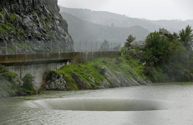 """After suffering through years of drought, California has received so much rain and snow this season that dams are being closely watched and reservoirs are threatening to overflow - except at Lake Berryessa, which has a giant """"glory hole"""" spillway draining 150 cubic feet of water per second into the creek below, drawing onlookers, TV cameras and a sky full of drones. (Eric Risberg/Associated Press)"""
