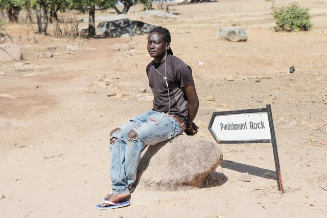 """A tour guide from the Pikoro Slave Camp in Ghana's Upper East demonstrates the use of the Punishment Rock; slaves who didn't submit were tied to the rock and left in the sun to die. New captives from Burkina Faso and Mali were held at camps like this one before being marched to one of the slave """"castles"""" on the coast."""
