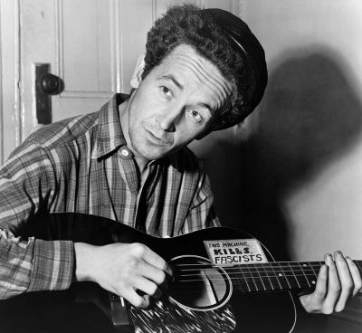"American folk singer Woody Guthrie in 1943; at the height of World War II his sign reads, This Machine Kills Fascists."" (Al Aumiller/New York World-Telegram and The Sun)"